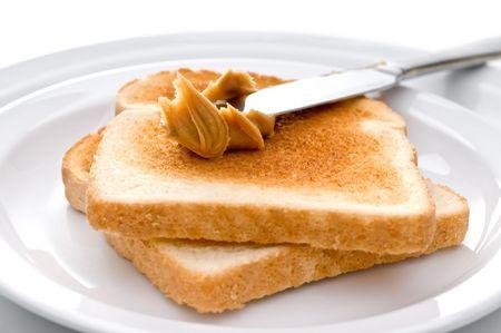 Spreading peanut butter on toast Imagens - 3865928