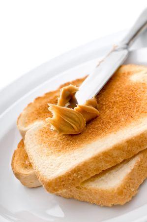 La difusi�n de mantequilla de man� sobre pan tostado