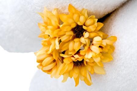 Yellow flowers and white towels Фото со стока