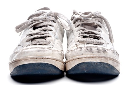 A pair of old worn athletic sports shoes on a white background