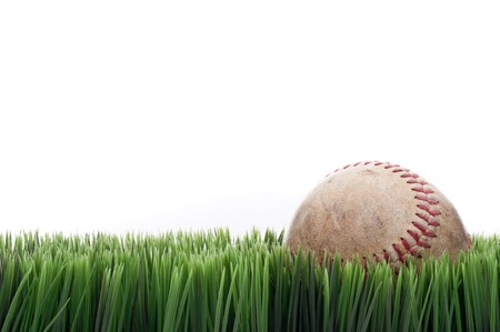 fescue: A worn leather baseball in grass with a white background