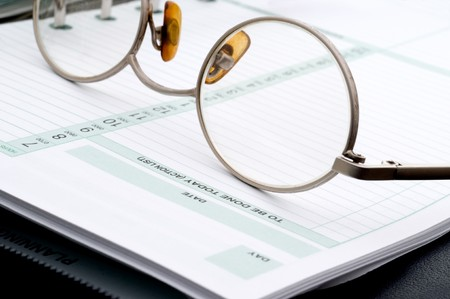 eye glasses on a business day planner