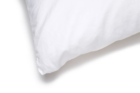 Corner edge of a white bed pillow on a white background