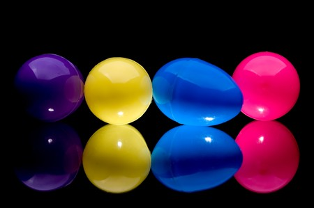 Four colorful plastic Easter eggs on a reflective surface Stock Photo - 4264266