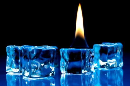 Hot flame burning on cold blue ice cubes on a reflective surface