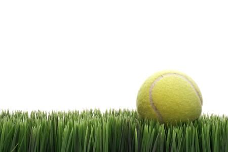A yellow tennis ball on green blades of grass
