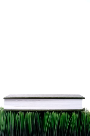 fescue: Green hardcover book sitting on grass with a white background with space for copy Stock Photo