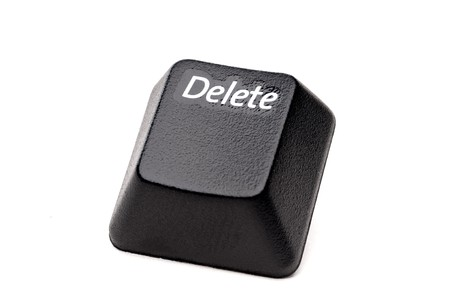 A horizontal closeup of a Delete button from a computer keyboard on white