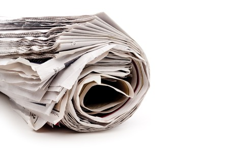 Horizontal view of a rolled up newspaper on white Imagens
