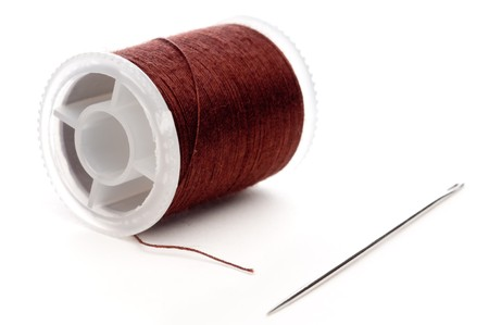 Horizontal extreme closeup of a spool of brown thread and a needle
