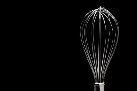 A silver stainless steel whisk on a black background