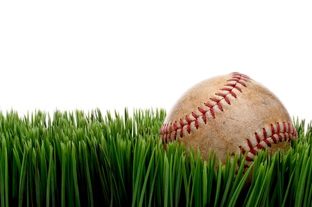 Horizontal view of an old worn sports baseball on grass against a white background