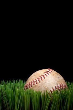 Vista vertical de un viejo deporte del b�isbol usado en el c�sped contra un fondo negro Foto de archivo