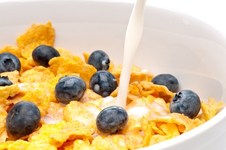 Horizontal view of pouring white milk into a bowl of breakfast flakes with blueberries