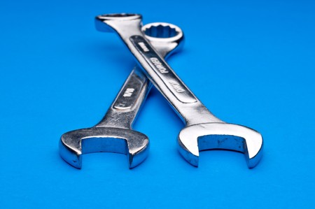 Horizontal image of a pair of old worn comnination wrenches on a blue background