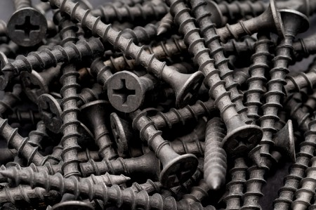 metal fastener: Macro of dark grey coarse thread drywall fastening screws Stock Photo