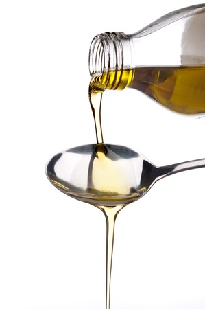 Pure virgin olive oil being poured out of a glass bottle onto a fork