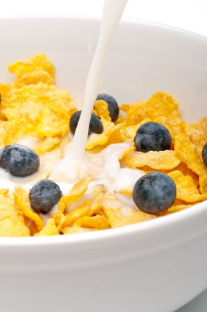 vertical view of pouring white milk into a bowl of breakfast flakes with blueberries
