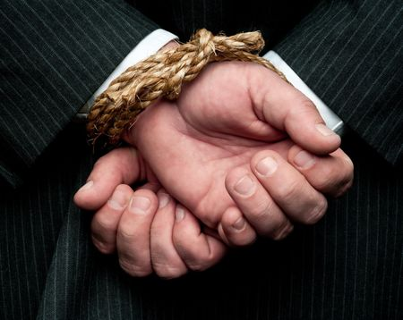 A horizontal view of a business man with his hands tied behind him. Concept: