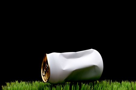 A horizontal image of a white crushed soda can tossed on green grass instead of being recycled