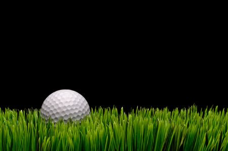 Horizontal image of a white golf ball in green grass on a black  background with space for copy