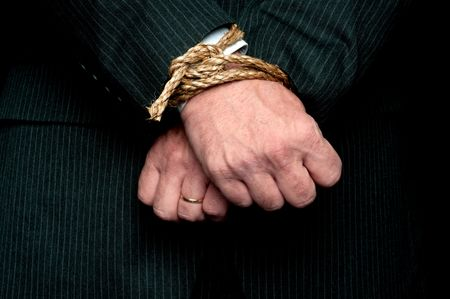 A horizontal view of a business man with his hands tied infront of him. Concept: