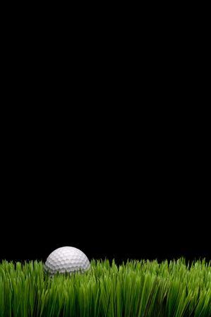 vertical: Vertical de la imagen de una pelota de golf blanca en la hierba verde sobre fondo negro con espacio para la copia
