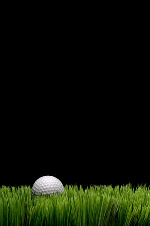Vertical image of a white golf ball in green grass on a black  background with space for copy