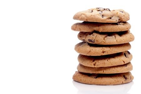 a horizontal image of a stack of 7 chocolate chip cookies on a white reflective surface with space for copy Stock Photo