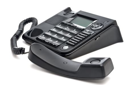 horizontal closeup of a black business telephone with the reciever off the hook