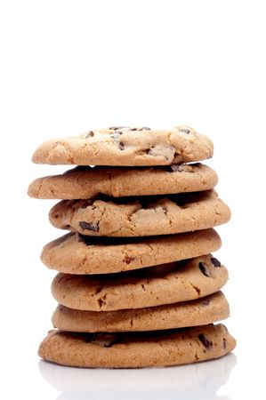 Vertical image of a stack of 7 chocolate chip cookies on a white reflective surface Stock Photo