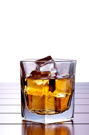 A vertical image of a glass of whiskey with ice on a wooden bar table with a white background and space for copy