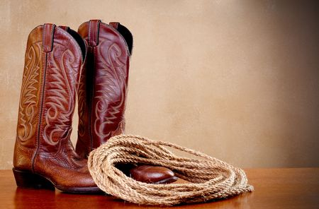 a horizontal image of a pair of brown cowboy boots and a coil of rope on a wooded surface with an old textured background