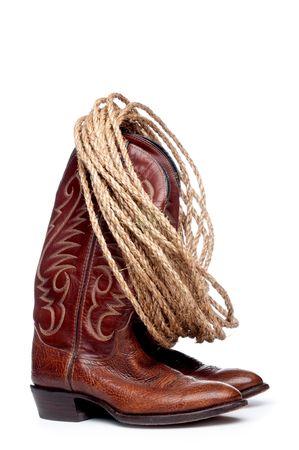 Verticale l'immagine di un paio di stivali da cowboy marrone e una bobina di corda su uno sfondo bianco Archivio Fotografico - 4805209