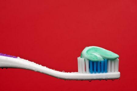 a horizontal closeup of a manual toothbrush with a glob of toothpaste and water droplets on a red background Stock Photo