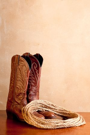 a vertical image of a pair of brown cowboy boots and a coil of rope on a wooded surface with an old textured background