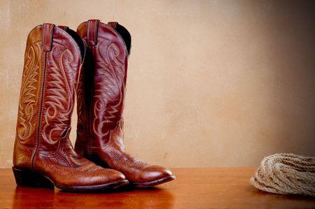 una horizontal de la imagen de un par de botas de cowboy marr�n y una bobina de cuerda en una superficie arbolada con una textura de fondo antiguo