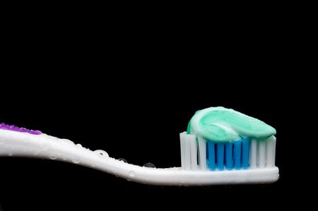 a horizontal closeup of a manual toothbrush with a glob of toothpaste and water droplets on a black background