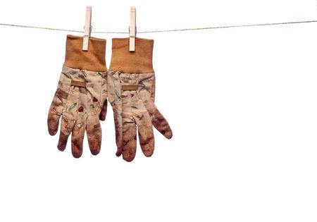 a horizontal image of dirty garden work gloves hanging on a clothes line