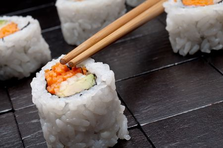 a tilted horizontal shallow focus macro of sushi with chopsticks on a black wooden background