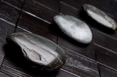 Tilted horizontal shallow focus image of 3 river rocks on black wood Stock fotó