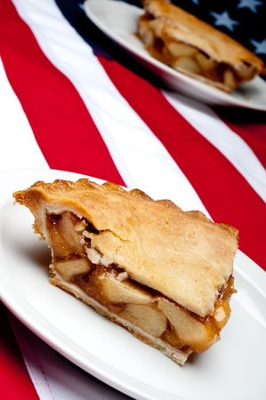 Shallow focus tilted vertical image of 2 pcs of apple pie on the American flag Stock fotó