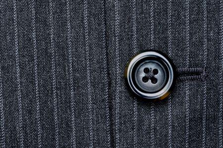 Cerca de un bot�n en un abrigo de traje de rayas de negocio de pin