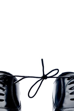 Vertical close up of a pair of black leather business shoes with laces tied together