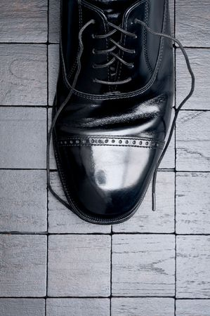 untied: A black leather business shoe with laces untied
