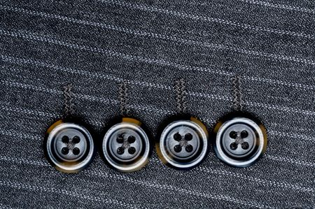 Close up of four buttons on a pin-striped suit jacket