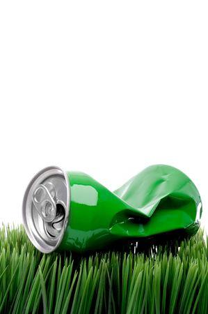 crushed aluminum cans: vertical de cerca de un verde aplastado aluminio puede beber en la hierba Foto de archivo