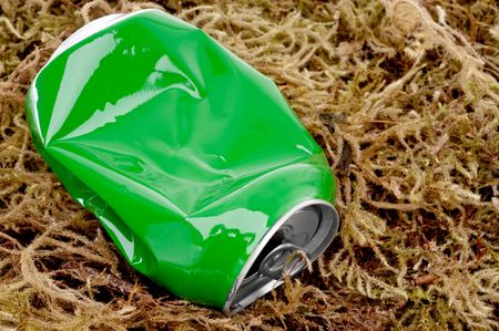 horizontal close up of a crushed green aluminum drink can on moss photo