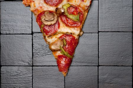 A slice of pizza on a black wooden background Stock Photo
