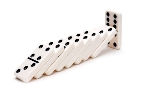 Horizontal image of falling dominoes on white